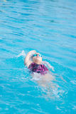 Woman in goggles swimming back crawl style Royalty Free Stock Images