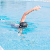 Woman in goggles swimming front crawl style. Young girl in goggles and cap swimming front crawl stroke style in the blue water pool Royalty Free Stock Photography