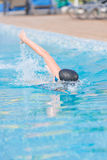 Woman in goggles swimming front crawl style. Young girl in goggles and cap swimming front crawl stroke style in the blue water pool Stock Photos
