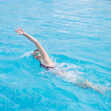 Woman in goggles swimming front crawl style. Young girl in goggles and cap swimming front crawl stroke style in the blue water pool Stock Photo