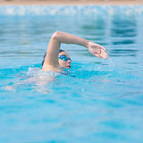 Woman in goggles swimming front crawl style. Young girl in goggles and cap swimming front crawl stroke style in the blue water pool Stock Photography