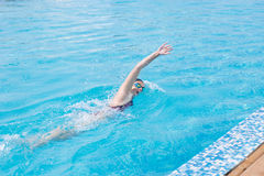 Woman in goggles swimming front crawl style Stock Images