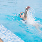 Woman in goggles swimming front crawl style Royalty Free Stock Images
