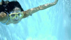 Woman in goggles swimming underwater stock video