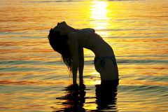 Woman is going activities yoga in Baltic sea. On a background sunset Royalty Free Stock Images