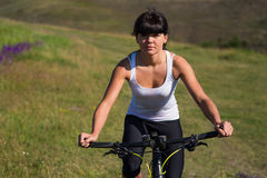 Woman going for bike ride on sunny day in countryside Royalty Free Stock Image