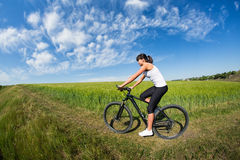 Woman going for bike ride on sunny day in countryside Royalty Free Stock Photos