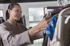 Woman going through clothes at fashion store Stock Images