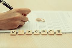 Woman going through divorce and signing papers. In the foreground the word - Divorce. toned Stock Photography