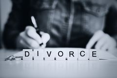 Woman going through divorce and signing papers. In the foreground the word - Divorce. toned Royalty Free Stock Photo