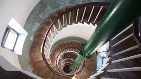 Woman going down by spiral stairs stock video