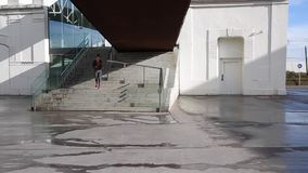 Woman going down stairs and running by the city stock video footage