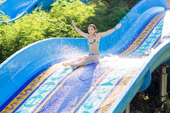 Woman going down a water slide Stock Image
