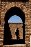 Woman going through the gateway in Alcazaba castle Royalty Free Stock Images