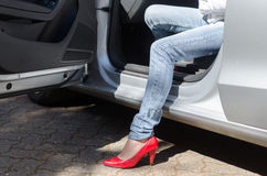 Woman going out of a car Royalty Free Stock Image