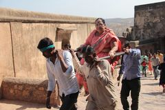 Woman going in Palanquin in India. A old woman is carried in palanquin by four man carrier hard working labor in hot sun uphill on Ranthambor Fort in Sawai Stock Photos