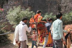Woman going in Palanquin in India. A old woman is carried in palanquin by four man carrier hard working labor in hot sun uphill on Ranthambor Fort in Sawai Royalty Free Stock Images