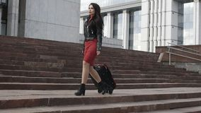 Woman is going with red suitcase stock footage
