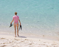 Woman going snorkeling. Young woman walking into tropical water to go snorkeling Stock Image