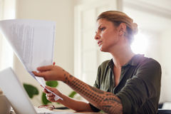 Woman  going through some paperwork at home Stock Photos