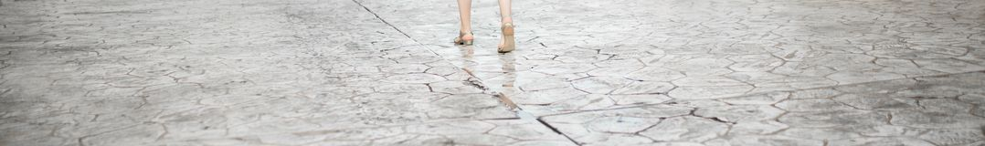 Woman is going on the street. Legs crop. Texture of the old road with cracks. Asphalt surface on the street. Web banner Stock Photography