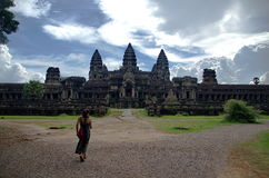 Woman going to Ankor wat temple. Woman going to Ankor wat main temple with stunning cloudy day Royalty Free Stock Photos