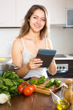 Woman going to cook the food. Woman with tablet in her hand going to cook the food stock photography