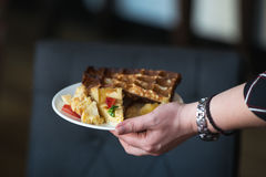 Woman is going to eat Belgian waffles, brunch in a restaurant. plate in hand Stock Image