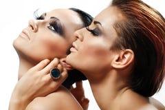 Woman going to kiss her girlfriend. Attractive women sharing their secrets, studio shot Stock Image
