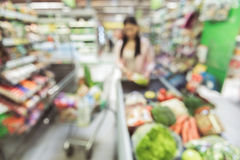 Woman going to pay for chosen goods. Adult female person is putting food on cash register tape in supermarket. Defocused picture of different products. Copy royalty free stock photo