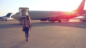 Woman going to plane an aerodrome Stock Images