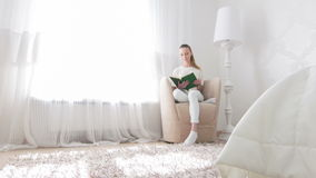 Woman going to read in her bedroom stock video footage