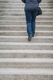 Woman going up on dirty concrete stairs Royalty Free Stock Images