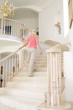 Woman going up staircase in luxurious home Royalty Free Stock Image