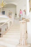 Woman going up staircase in luxurious home Stock Photo