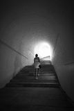 Woman going up the stairs at tunnel with light in the end Stock Image