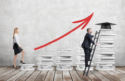 A woman is going up using a stairs which are made of white books to reach graduation hat while a man has found a shortcut to get e Royalty Free Stock Image