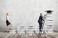 A woman is going up using a stairs which are made of white books to reach graduation hat while a man has found a shortcut to get e stock photos