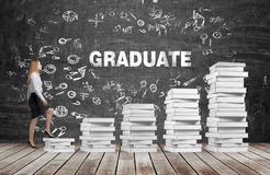 A woman is going up using a stairs which are made of white books. The word graduate is on the black chalkboard. Stock Photos