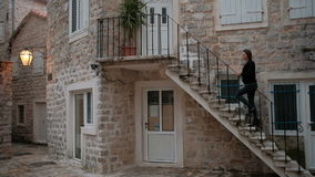 Woman going upstairs on open stairs in old town outdoors. Slow motion brunette female in jeans with boots black jacket walking on ancient city rises to top of stock video footage