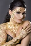 Woman in gold Stock Photography