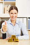 Woman with gold bars holding thumbs up Royalty Free Stock Images