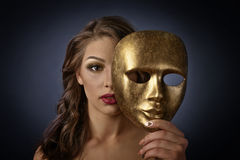 Woman with gold carnival mask on a black background Stock Images