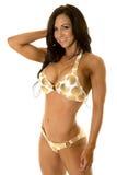 Woman in gold dot bikini smile hand behind head Stock Photo