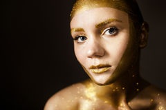 Woman with gold face make up Stock Images