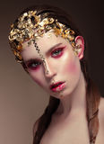 Woman with gold face make up. Stock Images