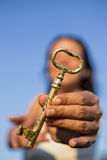 Woman gold key in hand blue sky Stock Images