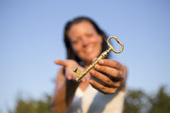 Woman gold key in hand blue sky. Nature picture with gold key in hand of women, she give to you a key of happyness Stock Photos