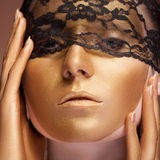 Woman with gold make up and lace on face Royalty Free Stock Photos