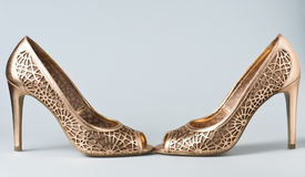 Woman gold shoes on background. Woman gold shoes on gray background Royalty Free Stock Photography